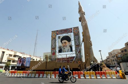 A Shahab-3 surface-to-surface missile is on display next to a portrait of Iranian Supreme Leader Ayatollah Ali Khamenei at a street exhibition by Iran's army and paramilitary Revolutionary Guard celebrating 'Defence Week' marking the 39th anniversary of the start of 1980-88 Iran-Iraq war, at the Baharestan Squer in Tehran, Iran, 26 September 2019. Media reported as tension between Iran and US going on, Iranian president Hassan Rouhani said in his speech at the 74th session of the General Assembly of the United Nations in New York that Iran will not negotiate with US under pressure and sanctions.