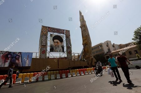 Iranians walk past as a Shahab-3 surface-to-surface missile is on display next to a portrait of Iranian Supreme Leader Ayatollah Ali Khamenei at a street exhibition by Iran's army and paramilitary Revolutionary Guard celebrating 'Defence Week' marking the 39th anniversary of the start of 1980-88 Iran-Iraq war, at the Baharestan Squer in Tehran, Iran, 26 September 2019. Media reported as tension between Iran and US going on, Iranian president Hassan Rouhani said in his speech at the 74th session of the General Assembly of the United Nations in New York that Iran will not negotiate with US under pressure and sanctions.