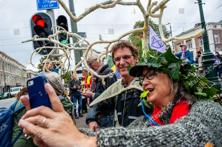 Stock Image of A woman wearing fake leaves on her head takes a selfie with a man during the demonstration. After Arnhem-based artist, Rob Voerman opened a petition to save the Amazon and to stop Bolsonaro which has already been signed more than 8,100 times, he organized a demonstration with other supporters in The Hague against the policies of Brazilian President, Jair Bolsonaro and against the Mercosur Free Trade Treaty. After the demonstration a petition was offered to the Brazilian ambassador and Sigrid Kaag, Minister for Foreign Trade and Development Cooperation.