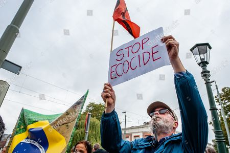 Stock Picture of A protester holding a placard while blowing a whistle during the demonstration. After Arnhem-based artist, Rob Voerman opened a petition to save the Amazon and to stop Bolsonaro which has already been signed more than 8,100 times, he organized a demonstration with other supporters in The Hague against the policies of Brazilian President, Jair Bolsonaro and against the Mercosur Free Trade Treaty. After the demonstration a petition was offered to the Brazilian ambassador and Sigrid Kaag, Minister for Foreign Trade and Development Cooperation.
