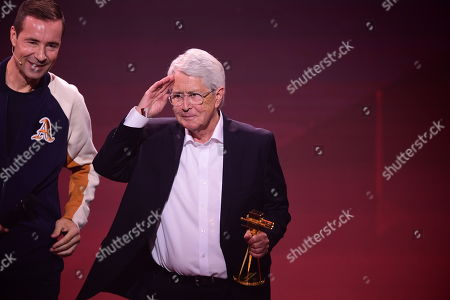 German TV host Frank Elstner (R) gestures after receiving the 'Best Newcomer' award from German TV host and laudator Kai Pflaume (L) during the 'YouTube Goldene Kamera Digital Award 2019' ceremony in Berlin, Germany, 26 September 2019. The best German web video producers are awarded at the event.