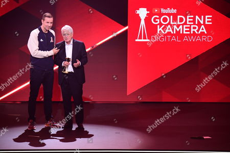 Stock Image of German TV host Frank Elstner (R) speaks after receiving the 'Best Newcomer' award from German TV host and Kai Pflaume (L) during the 'YouTube Goldene Kamera Digital Award 2019' ceremony in Berlin, Germany, 26 September 2019. The best German web video producers are awarded at the event.