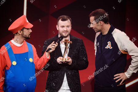 Stock Image of German YouTuber Domtendo (C) with his 'Best of Letâ??s Play and Gaming' award next to German TV host and laudator Kai Pflaume (R) and host Daniele Rizzo, dressed in a Super Mario costume, during the 'YouTube Goldene Kamera Digital Award 2019' ceremony in Berlin, Germany, 26 September 2019. The best German web video producers are awarded at the event.