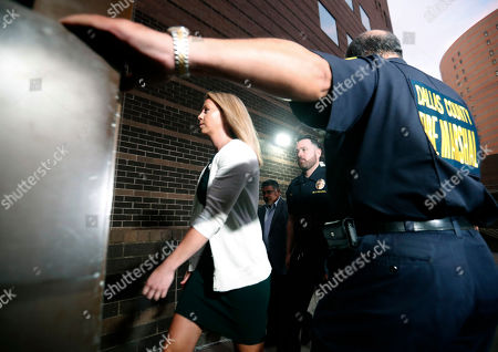 In this, Amber Guyger, center, walks flanked by security while arriving for her murder trial at the Frank Crowley Courthouse in downtown Dallas. Security has been ramped up around the white former Dallas police officer's high-profile trial for murder in the killing of her unarmed black neighbor. The Dallas Police Association says threats have forced the group to hire private security for Guyger and her lawyers