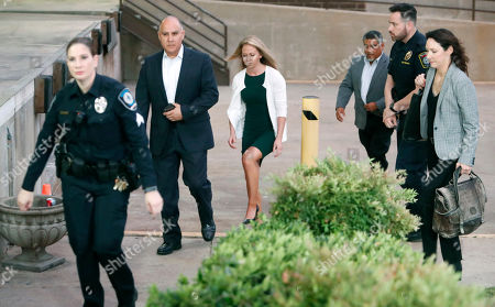 Amber Guyger, center, walks flanked by security while arriving for her murder trial at the Frank Crowley Courthouse in downtown Dallas. Security has been ramped up around the white former Dallas police officer's high-profile trial for murder in the killing of her unarmed black neighbor. The Dallas Police Association says threats have forced the group to hire private security for Guyger and her lawyers