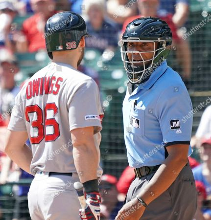 Boston Red Sox batter Chris Owings talks with umpire CB Bucknor after being called out on strikes in the third inning of a baseball game against the Texas Rangers, in Arlington, Texas
