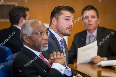 """Former """"Bachelor"""" star Chris Soules listens during a hearing in Buchanan County District Court with his lawyers on Monday, Nov. 27, 2017, in Independence, Iowa. Lawyers for Soules' have asked a judge to dismiss the charge against him stemming from his rear-end crash that killed a farmer driving a tractor. (Rodney White/The Des Moines Register via AP, Pool)"""