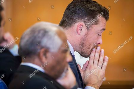 """Former """"Bachelor"""" star Chris Soules listens to his 911 call from the day of his rear-end crash during a hearing in Buchanan County District Court with his lawyers on Monday, Nov. 27, 2017, in Independence, Iowa. Lawyers for Soules' have asked a judge to dismiss the charge against him stemming from the crash that killed a farmer driving a tractor. (Rodney White/The Des Moines Register via AP, Pool)"""