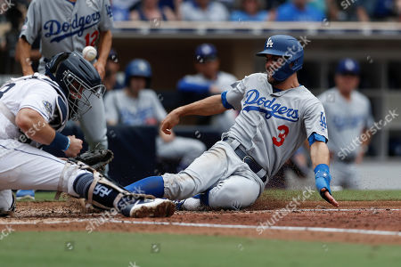 Los Angeles Dodgers' Chris Taylor, right, scores from first off a single by Max Muncy as San Diego Padres catcher Austin Hedges bobbles the ball during the sixth inning of a baseball game, in San Diego