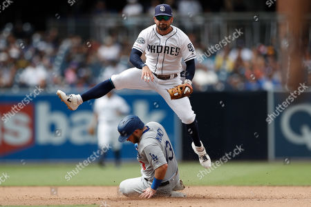 San Diego Padres second baseman Greg Garcia, above, leaps over Los Angeles Dodgers' Max Muncy after completing the double play during the ninth inning of a baseball game, in San Diego. Muncy was out at second and Enrique Hernandez was out at first on the play