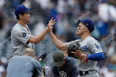 Los Angeles Dodgers relief pitcher Kenta Maeda, left, celebrates with shortstop Enrique Hernandez after defeating the San Diego Padres 1-0 in a baseball game, in San Diego