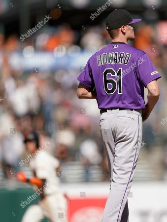 Colorado Rockies relief pitcher Sam Howard (61) walks on the mound as San Francisco Giants' Mauricio Dubon, back left, rounds the bases after hitting a solo home run in the seventh inning of a baseball game, in San Francisco