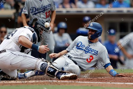 Los Angeles Dodgers' Chris Taylor, right, scores from first off a single by Max Muncy as San Diego Padres catcher Austin Hedges, left, bobbles the ball during the sixth inning of a baseball game, in San Diego