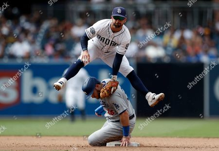 San Diego Padres second baseman Greg Garcia, top, leaps over Los Angeles Dodgers' Max Muncy after completing the double play during the ninth inning of a baseball game, in San Diego. Muncy was out at second and Enrique Hernandez was out at first on the play