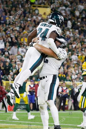 Philadelphia Eagles running back Jordan Howard (24) and center Jason Kelce (62) celebrate a touchdown during the first half of the team's NFL football game against the Green Bay Packers, in Green Bay, Wis