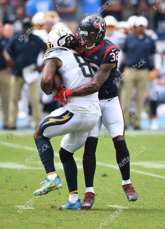 Stock Image of Lonnie Johnson Jr. - Mike Williams. Houston Texans cornerback Lonnie Johnson Jr. (32) tackles Los Angeles Chargers wide receiver Mike Williams (81) after Williams caught a pass during an NFL football game against the Chargers, in Carson, Calif. The Texans defeated the Chargers 27-20