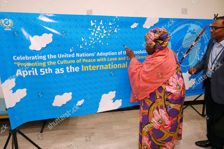 """Guests sign a banner celebrating the United Nations' adoption of a resolution designating April 5th as the """"International Day of Conscience"""" during the World Leader Summit of Love and Peace, at U.N. headquarters"""