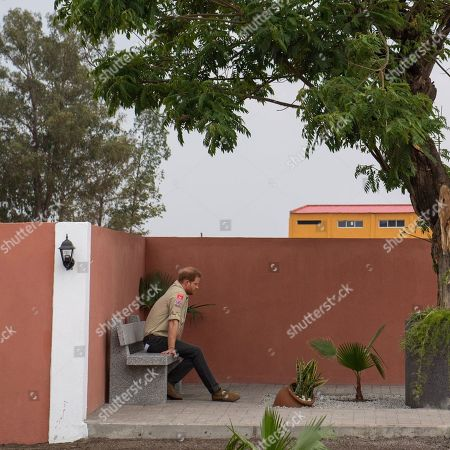 Stock Image of Prince Harry sits alone beneath the Diana Tree in Huambo, Angola, on day five of the royal tour of Africa. The Duke is visiting the minefield where his late mother, the Princess of Wales, was photographed in 1997, which is now a busy street with schools, shops and houses.