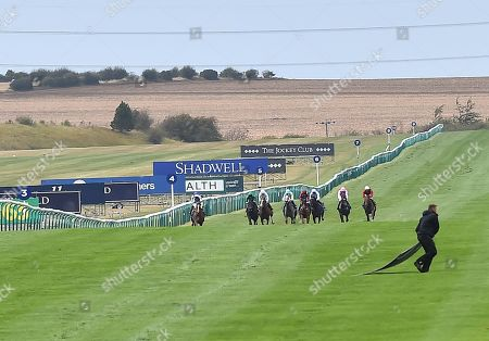 A brave member of the racecourse groundstaff rushes out to retrieve a piece of advertising hoarding which had blown onto the track as the runners in Princess Anne Muhaarar Stakes bear down on him.