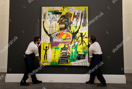 Stock Picture of Sotheby's employees arrange a painting by Jean-Michel Basquiat called Pyro on display at Sotheby's auction rooms in London, . The painting will be offered for sale on Oct. 3 in the Contemporary Art Evening Auction with the estimate on request