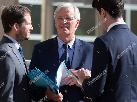 European Union chief Brexit negotiator Michel Barnier, center, goes through his papers as he waits outside of EU headquarters in Brussels for the arrival of Irish Foreign Minister Simon Coveney, . Michel Barnier is meeting with Irish Foreign Minister Simon Coveney and UK Brexit secretary Stephen Barclay seeking a way to unblock the stalled negotiations on Britain's withdrawal from the bloc