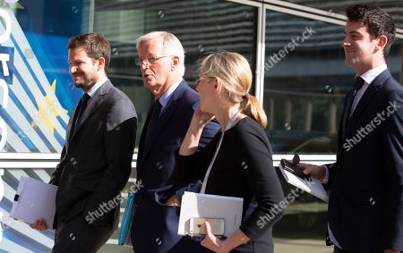 European Union chief Brexit negotiator Michel Barnier, second left, waits outside of EU headquarters in Brussels for the arrival of Irish Foreign Minister Simon Coveney, . Michel Barnier is meeting with Irish Foreign Minister Simon Coveney and UK Brexit secretary Stephen Barclay seeking a way to unblock the stalled negotiations on Britain's withdrawal from the bloc