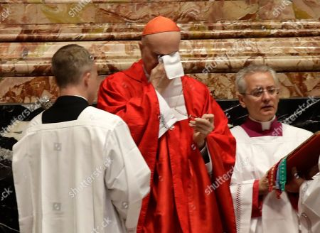 Stock Image of Cardinal Tarcisio Bertone wipes his eyes as he celebrates Mass at the funeral of late Cardinal William Joseph Levada, inside St. Peter's Basilica, at the Vatican