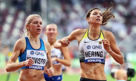 Sara Kuivisto (L) of Finland and Christina Hering (R) of Germany cross the finish line during the women's 800m heats at the IAAF World Athletics Championships 2019 at the Khalifa Stadium in Doha, Qatar, 27 September 2019.