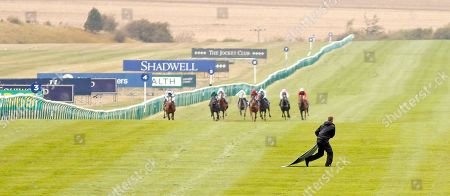 A racecourse groundsman retrieves an advertising hoarding from the track after it had blown into the path of the field for Princess Anne Muhaarar Stakes Newmarket