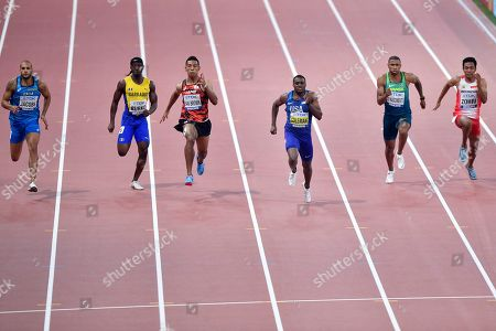 Christian Coleman of the U.S., center in blue, runs to finish under 10 seconds during the men's 100 meters heats during the World Athletics Championships, in Doha, Qatar, ahead of Lamont Marcell Jacobs of Italy, Barbados' Mario Burke, Japan's Abdul Hakim Sani Brown, from left, Brazil Rodrigo Do Nascimento, second right, and Indonesia's Lalu Muhammad Zohri