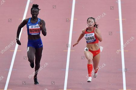 Tori Bowie, of the United States, and Xiaojing Liang, of China, right, compete in a women's 100 meter race heat during the World Athletics Championships in Doha, Qatar