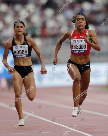 Zoe Hobbs, of New Zealand, and Mujinga Kambundji, of Switzerland, compete in a women's 100 meter heat at the World Athletics Championships in Doha, Qatar