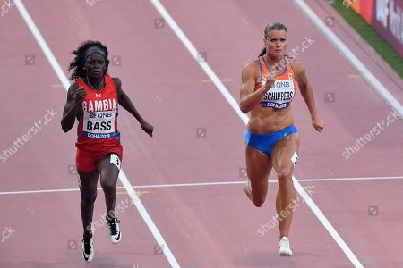 Dafne Schippers, of the Netherlands, and Gina Bass, of The Gambia, left, compete in a women's 100 meter race heat during the World Athletics Championships in Doha, Qatar