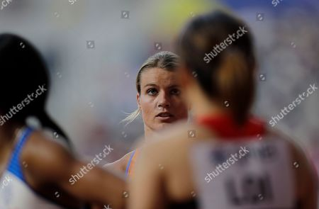 Dafne Schippers, of the Netherlands, talks with other athletes after a women's 100 meter heat at the World Athletics Championships in Doha, Qatar