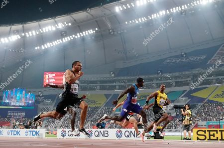 Andre De Grasse, of Canada, crosses the finish line ahead of Yohan Blake, of Jamaica, and Justin Gatlin, of the United States, in a men's 100 meter semifinal at the World Athletics Championships in Doha, Qatar