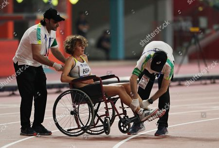 Alina Reh, of Germany is taken from the track after pulling out of the women's 10,000m final at the World Athletics Championships in Doha, Qatar