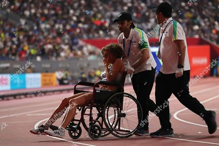 Alina Reh (L) of Germany receives medical assistance during the women's 10,000m final during the IAAF World Athletics Championships 2019 at the Khalifa Stadium in Doha, Qatar, 28 September 2019.