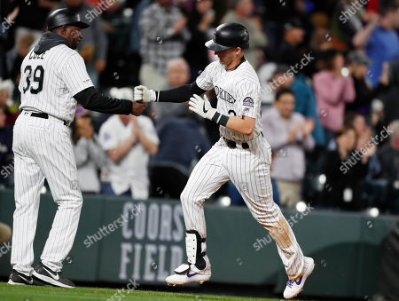 R m. Colorado Rockies third base coach Stu Cole, left, congratulates Ryan McMahon who circles the bases after hitting a two-run home run off Milwaukee Brewers relief pitcher Jake Faria in the seventh inning of a baseball game, in Denver