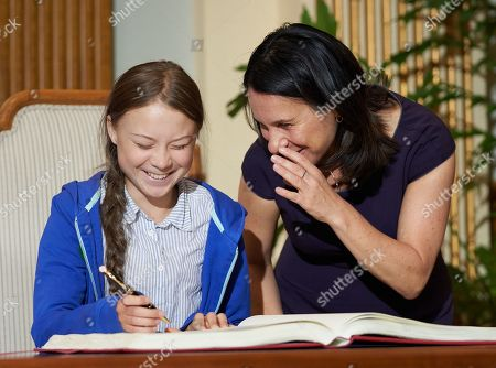 Swedish climate activist Greta Thunberg (L)  laughs as she signs the guest book after receiving the key to the city from the Mayor of Montreal Valerie Plante (R) following the climate strike in Montreal, Quebec, Canada, 27 September 2019. Thunberg participated in several climate events in Montreal, continuing a month-long series of climate-related appearances in the US and Canada which began with her sailing from England to New York in late August.