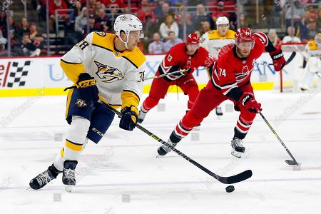Nashville Predators Jeremy Davies (38) brings the puck upice after taking it away from Carolina Hurricanes' Jaccob Slavin (74) during the third period of an NHL preseason hockey game in Raleigh, N.C