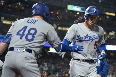 Los Angeles Dodgers' Corey Seager (5) is congratulated by teammate Gavin Lux (48) after he hit a solo home run against the San Francisco Giants during the second inning of a baseball game, in San Francisco