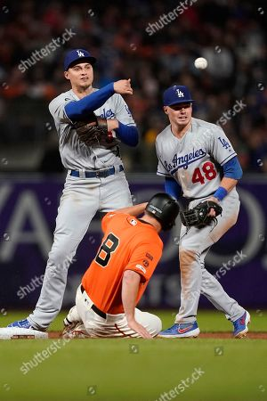 Los Angeles Dodgers shortstop Corey Seager (5) throws to first base after forcing out San Francisco Giants' Alex Dickerson (8) as shortstop Gavin Lux (48) looks on during the seventh inning of a baseball game, in San Francisco. Brandon Crawford was save at first base