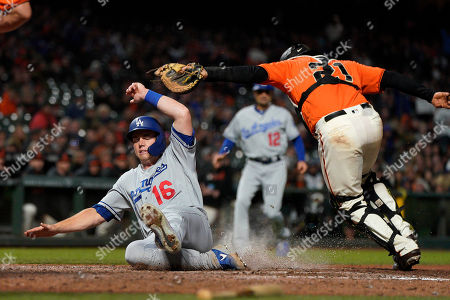 Los Angeles Dodgers' Will Smith (16) beats the tag by San Francisco Giants catcher Stephen Vogt (21) to score on a single by Enrique Hernandez during the eighth inning of a baseball game, in San Francisco
