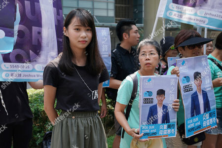 Joshua Wong, Agnes Chow. Hong Kong democratic activist Agnes Chow, stands next to the election campaign posters of democratic activist, Joshua Wong, in Hong Kong, . Wong announced plans to contest local elections and warns that any attempt to disqualify him will only spur more support for monthslong pro-democracy protests