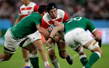 Japan's James Moore runs at Ireland's CJ Stander, left, and Rhys Ruddock, right, during the Rugby World Cup Pool A game at Shizuoka Stadium Ecopa between Japan and Ireland in Shizuoka, Japan