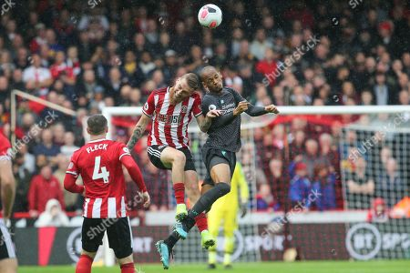 Liverpool midfielder Fabinho (3) and Sheffield United forward Oli McBurnie (9) challenge for the ball during the Premier League match between Sheffield United and Liverpool at Bramall Lane, Sheffield