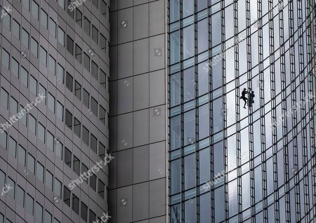"""French urban climber Alain Robert, well known as """"Spiderman"""", climbs down the 'Skyper' highrise in Frankfurt, Germany"""