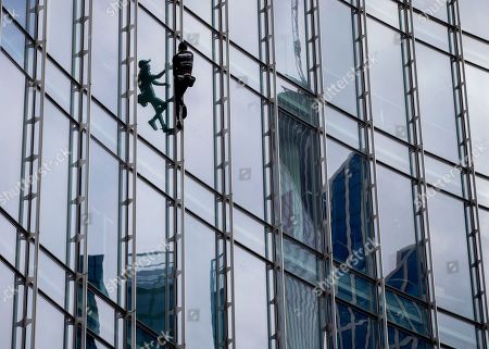 """French urban climber Alain Robert, well known as """"Spiderman"""", climbs up the 'Skyper' highrise in Frankfurt, Germany"""