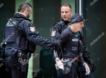 """French urban climber Alain Robert, well known as """"Spiderman"""", is escorted by police officers after climbing the 'Skyper' highrise in Frankfurt, Germany"""