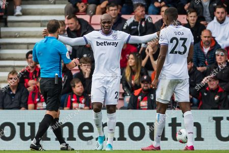 Angelo Ogbonna (West Ham) with Stuart Attwell (Referee) & Issa Diop (West Ham) looking on as he raises his arms during the Premier League match between Bournemouth and West Ham United at the Vitality Stadium, Bournemouth